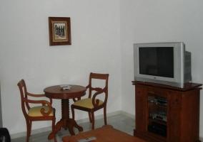 Televisor sobre mueble con DVD y aparato digital en sala de estar