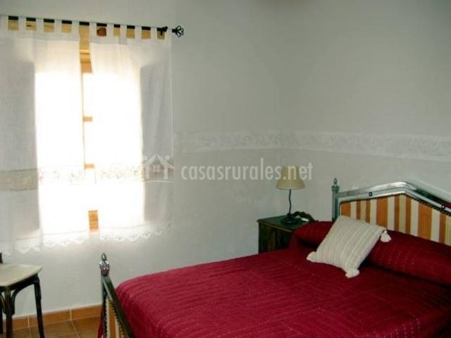 Dormitorio con cama roja de matrimonio