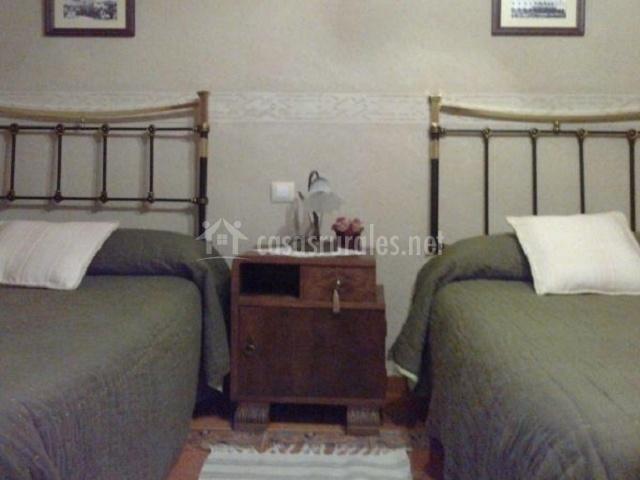 Dormitorio con cuadros sobre las camas verdes