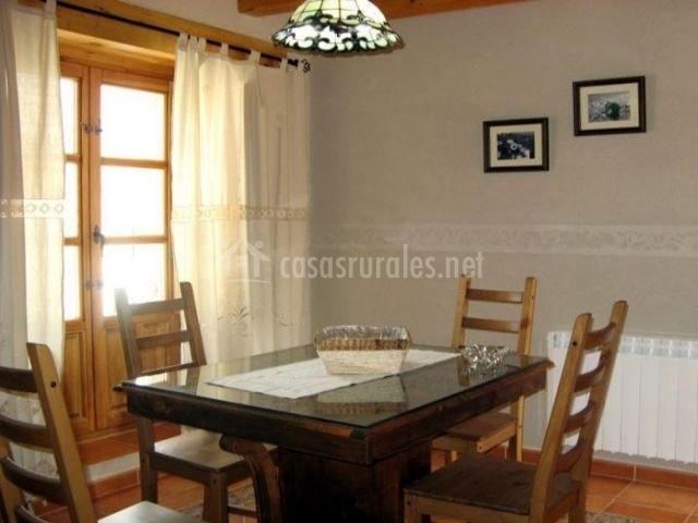 Mesa de comedor con cristal encima y sillas de madera