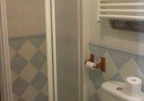 Aseo con azulejos blancos y azules y ducha