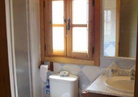 Aseo con inodoro junto al lavabo y espejo encima