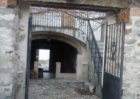 Entrada a la casa con patio empedrado y escaleras