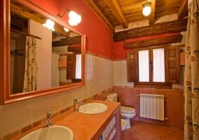 Aseo con dos lavabos y espejo grande colgado encima