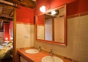 Aseo de dormitorio con azulejos blancos y paredes rojas