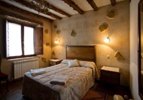 Dormitorio con cama doble y detalles de piedra en las paredes