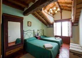 Dormitorio con dos camas verdes y armario con espejo