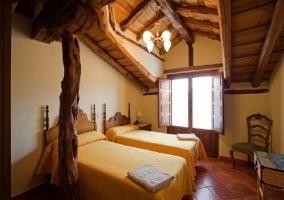 Dormitorio con techo abuhardillado y columna de madera