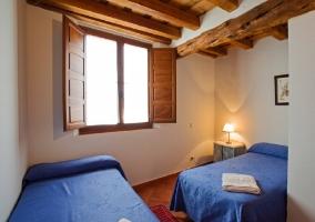 Dormitorio doble con dos camas azules y ventana con puertas