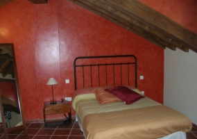 Dormitorio con techo abohardillado
