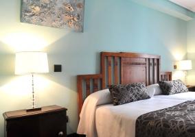 Dormitorio con pared roja y dos camas con estampado de flores