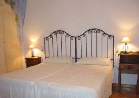 Dos camas separadas en dormitorio con cortina roja