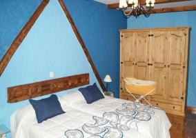 Dormitorio con dos camas y cabecero azul triangular