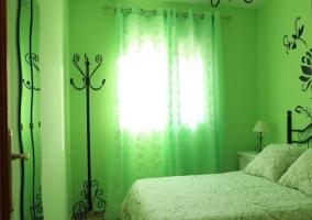 Dormitorio con paredes en verde y decoración en negro