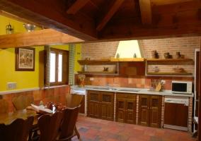 Cocina con lavavajillas y microondas y mesa de comedor
