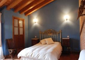 Dormitorio de matrimonio con paredes azules y abuhardillado