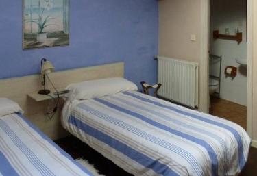 Dormitorio doble con dos camas y carto de baño