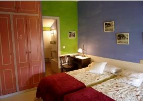 Dormitorio doble con dos camas y paredes de colores