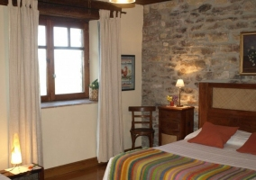Habitación matrimonio con paredes de piedra