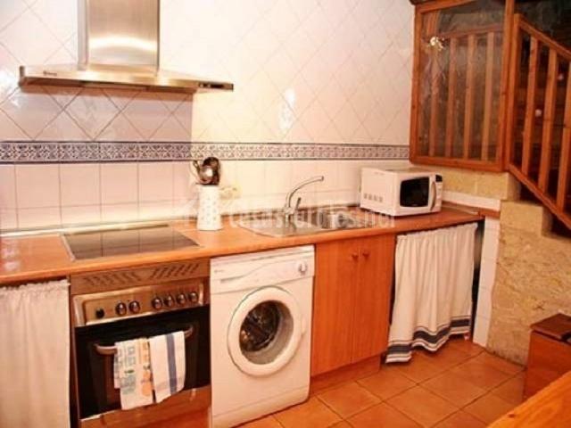 Cocina con encimera de madera y lavadora