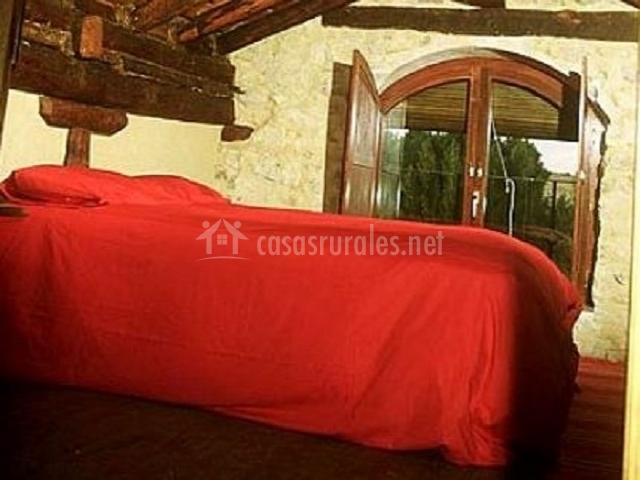 Dormitorio de matrimonio en buhardilla con ventana abierta
