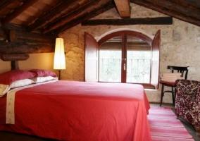 Dormitorio abuhardillado con dos sillones delante de la cama