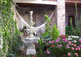 Porche con columnas de piedra y hamaca