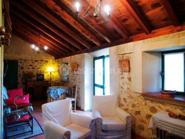 Sala de estar con sillones y techo abuhardillado
