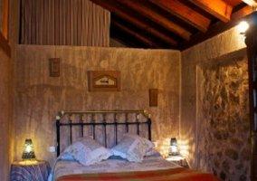Techo abuhardillado y de madera en dormitorio de matrimonio