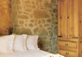 Dormitorio de matrimonio con paredes de piedra y armario de madera