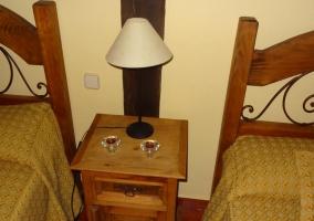 Habitación doble con camas individuales y pequeña cómoda con lámpara