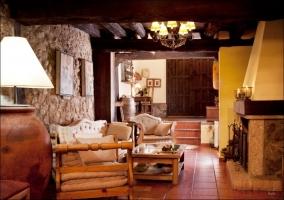 Salón con chimenea, paredes de piedra y techos de madera con viga