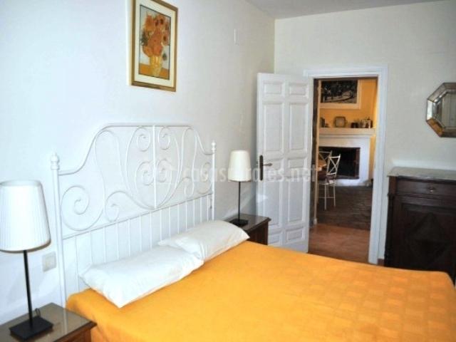 Dormitorio amarillo con cabecero en hierro forjado blanco
