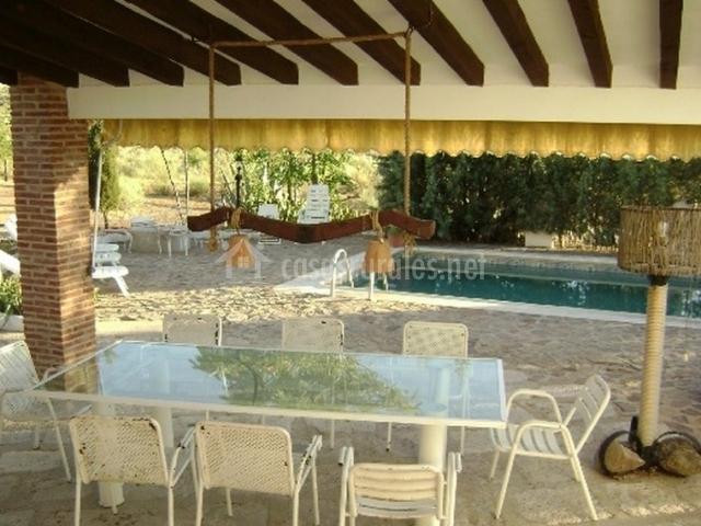 Mesa de exterior y piscina de la casa rural