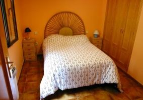 Dormitorio con cama de matrimonio y paredes naranjas