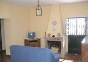 Sala de estar con mueble esquinero junto a la chimenea