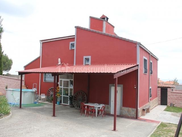 Vistas de la fachada en tonos rojos con porche