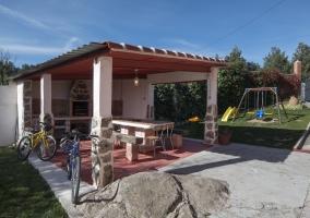 Barbacoa con muebles de jardín y zona de juegos para los más pequeños