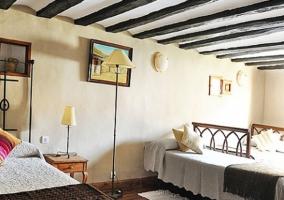 Habitación de paredes blancas con camas supletorias