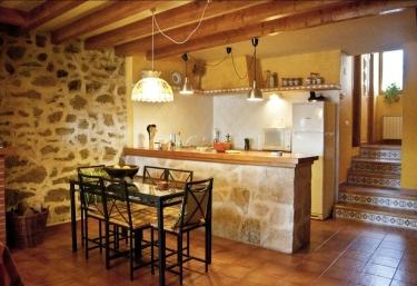 Cocina con barra en piedra y mesa de forja