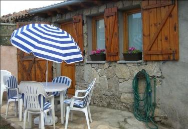 Exterior de la vivienda en piedra y madera con mesa y sombrilla