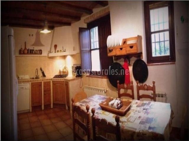Cocina con mesa vigas de madera y utensilios