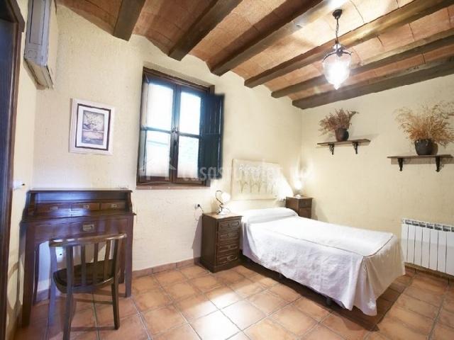Habitación individual con vigas de madera en el techo y mobiliario de madera