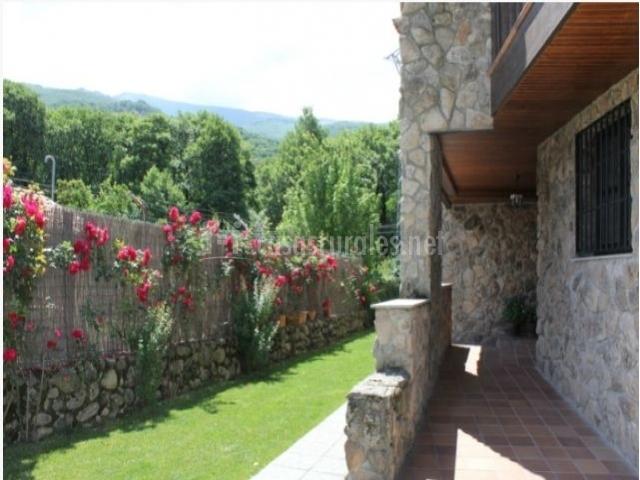 Patio exterior con piedras y vallas con flores