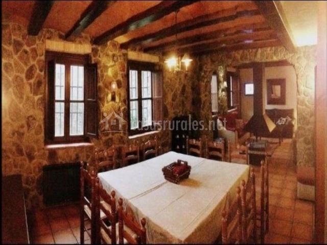 Salón de piedra con vigas de madera y mesa