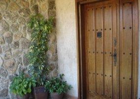 Entrada a la casa puerta de madera y macetas
