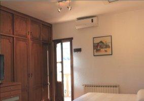 Habitación con armarios de madera y cama blanca