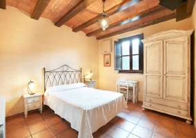 Habitación de matrimonio con suelo marrón, vigas de madera y edredón blanco