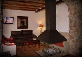 Salón con sofás y chimenea colgante
