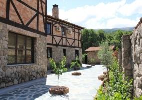 Vista de la casa y todo el jardín con árboles y fachada de piedra